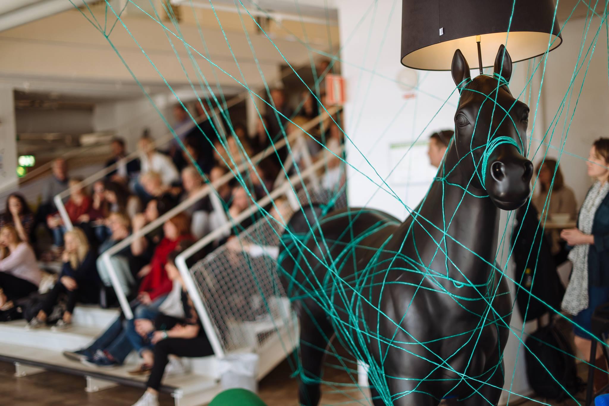 Bilden visar en svart plasthäst med en lampskärm. Runt hästen är det trådar som går åt olika håll. I bakgrunden sitter en stor grupp människor i en trappa