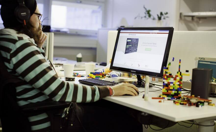 Bilden visar en person som sitter framför sin dator och arbetar vid ett skrivbord. På skrivbordet står det lego och kaffekoppar.