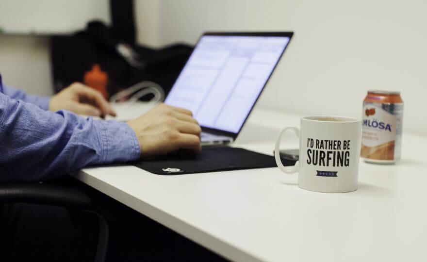 Bilden visar ett kontorsbord med en dator, kaffekopp och burk med vatten på. Vid datorn sitter en person.