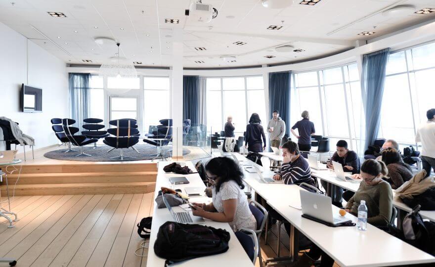 Bilden visar en lokal där flera människor sitter vid borden och arbetar vid sina datorer. I bakgrunden står en grupp och pratar.