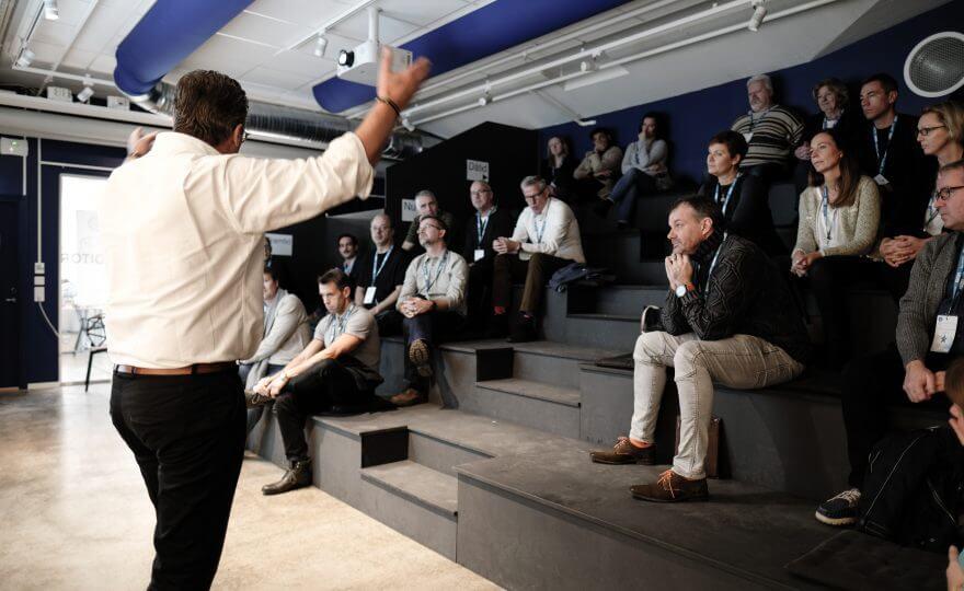 Bilden visar en föreläsningslokal där en person föreläser för en grupp människor