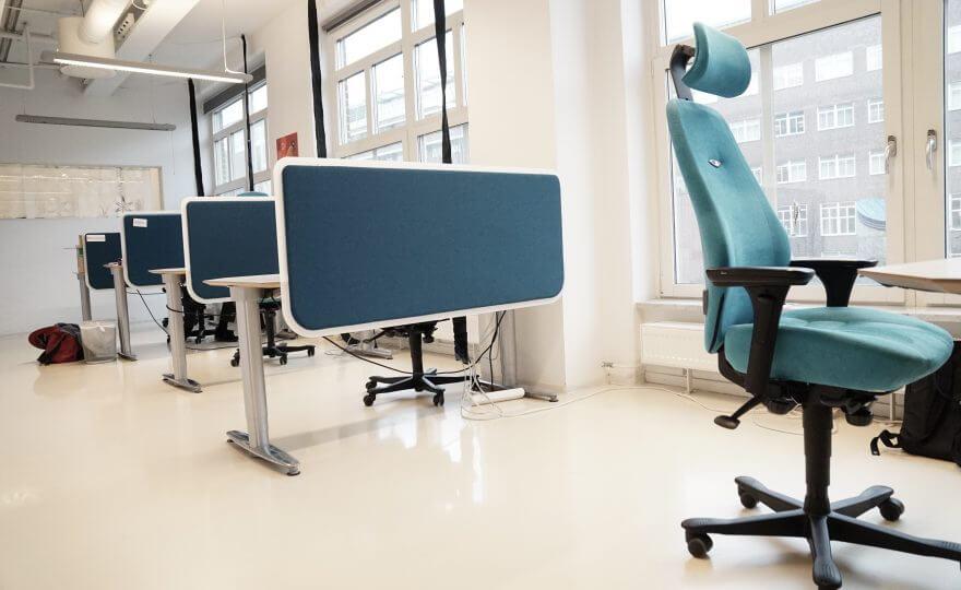 Bilden visar ett öppet kontor med flera skrivbord och kontorsstolar