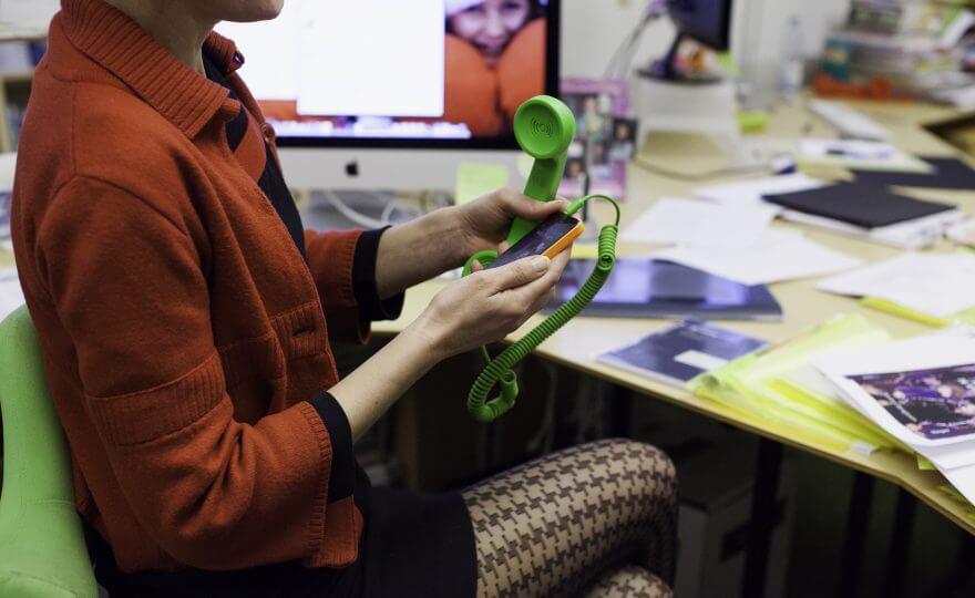 Bilden visar en kvinna som sitter vid ett skrivbord med sin mobil