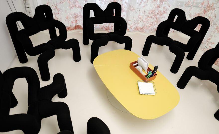 Bilden visar ett rum med ett gult bord i mitten och flera svarta designerstolar runt