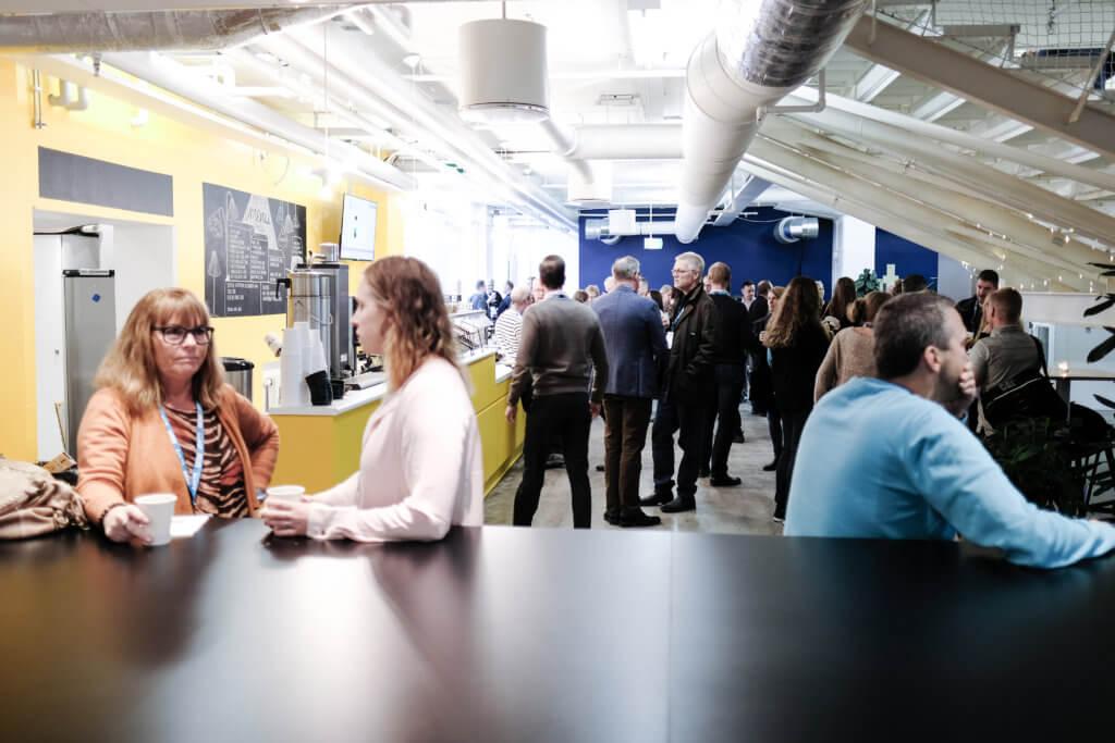 Bilden visar ett stort rum med människor som står och pratar i olika grupper