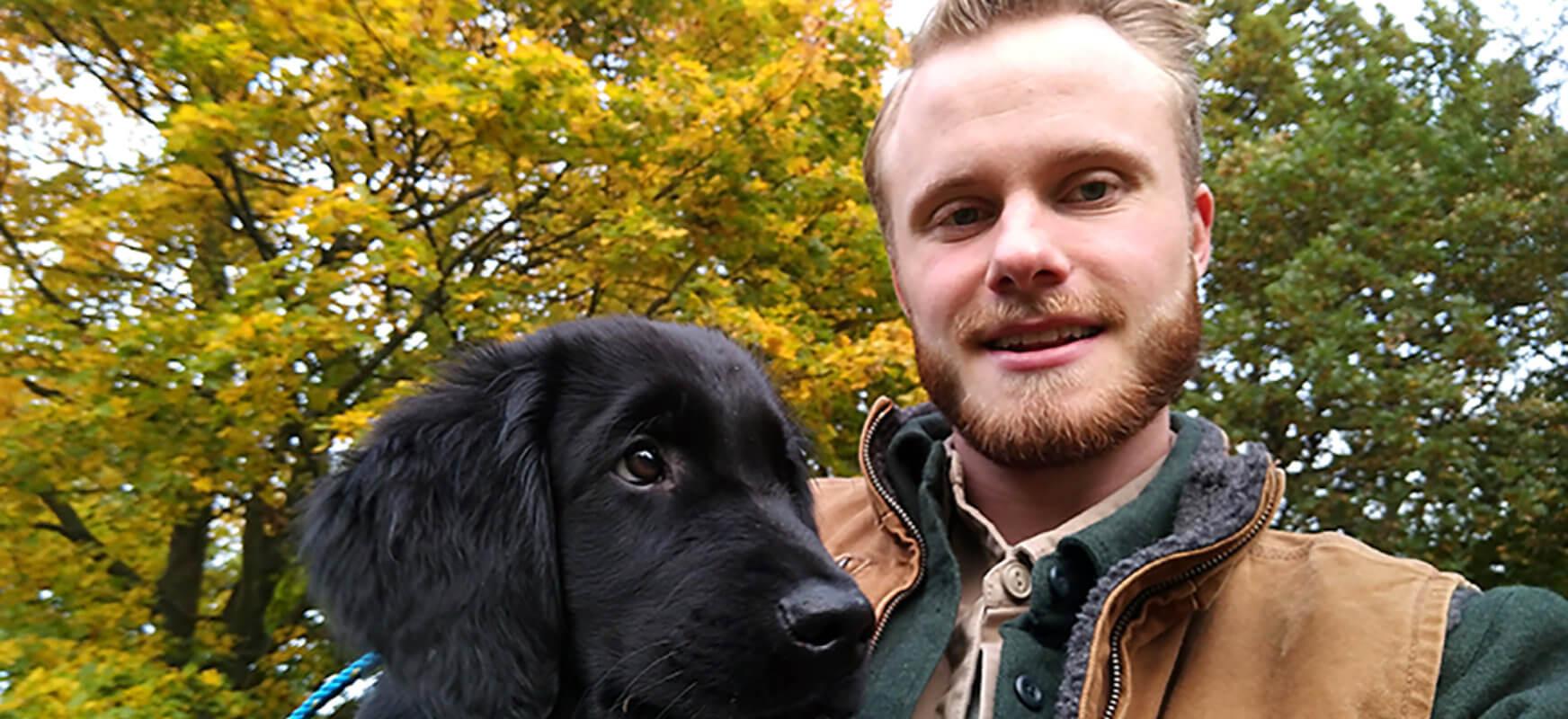 Jakob Gelberg med en svart hundvalp