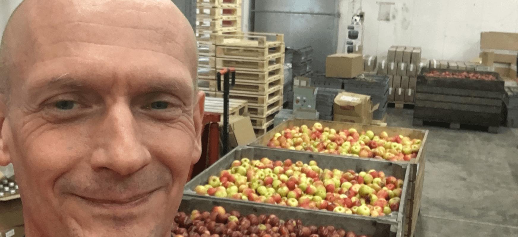 Göran Tollstam framför en stor mängd äpplen