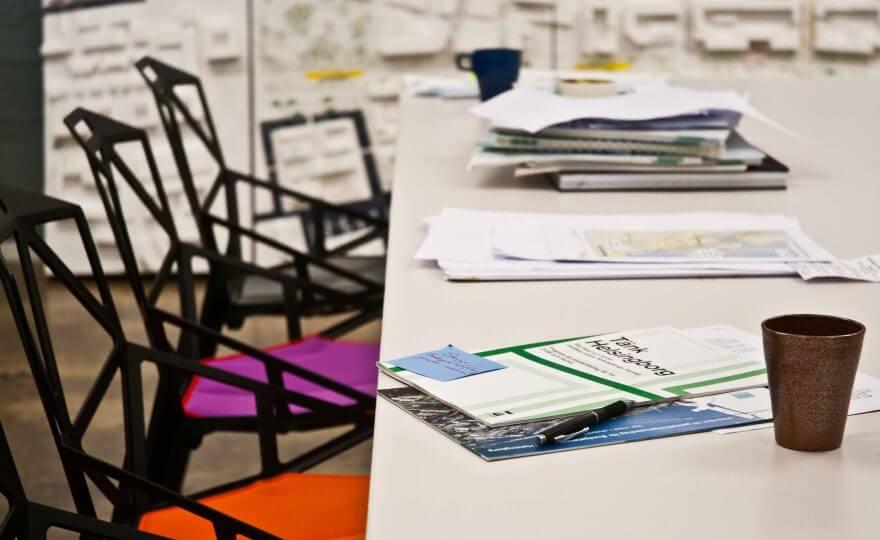 Bilden visar ett vitt bord med papper och dokument på. Det står även två kaffekoppar. Bredvid bordet finns flera stolar med färgglada dynor i.