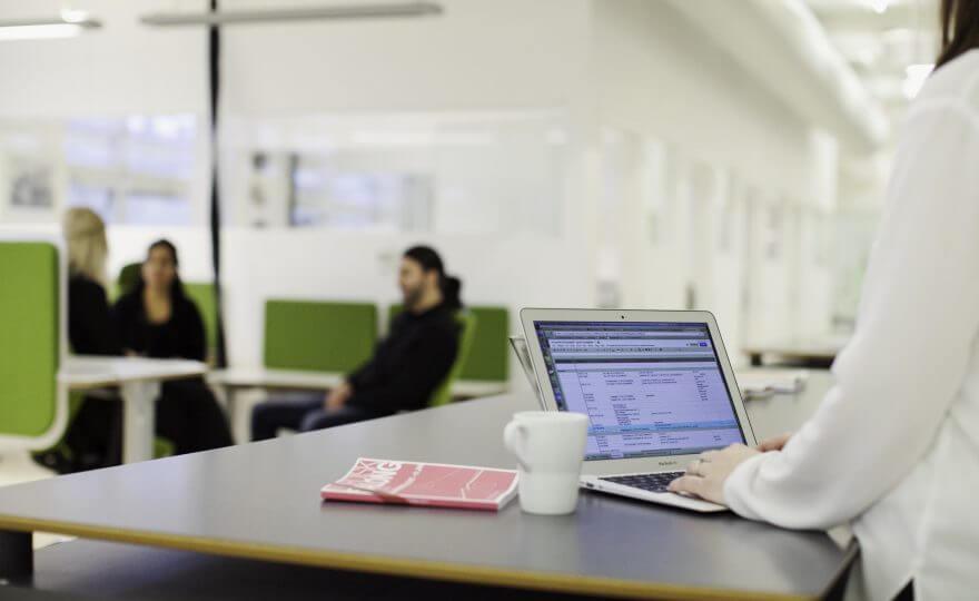 Bilden visar en person som står framför en dator och arbetar
