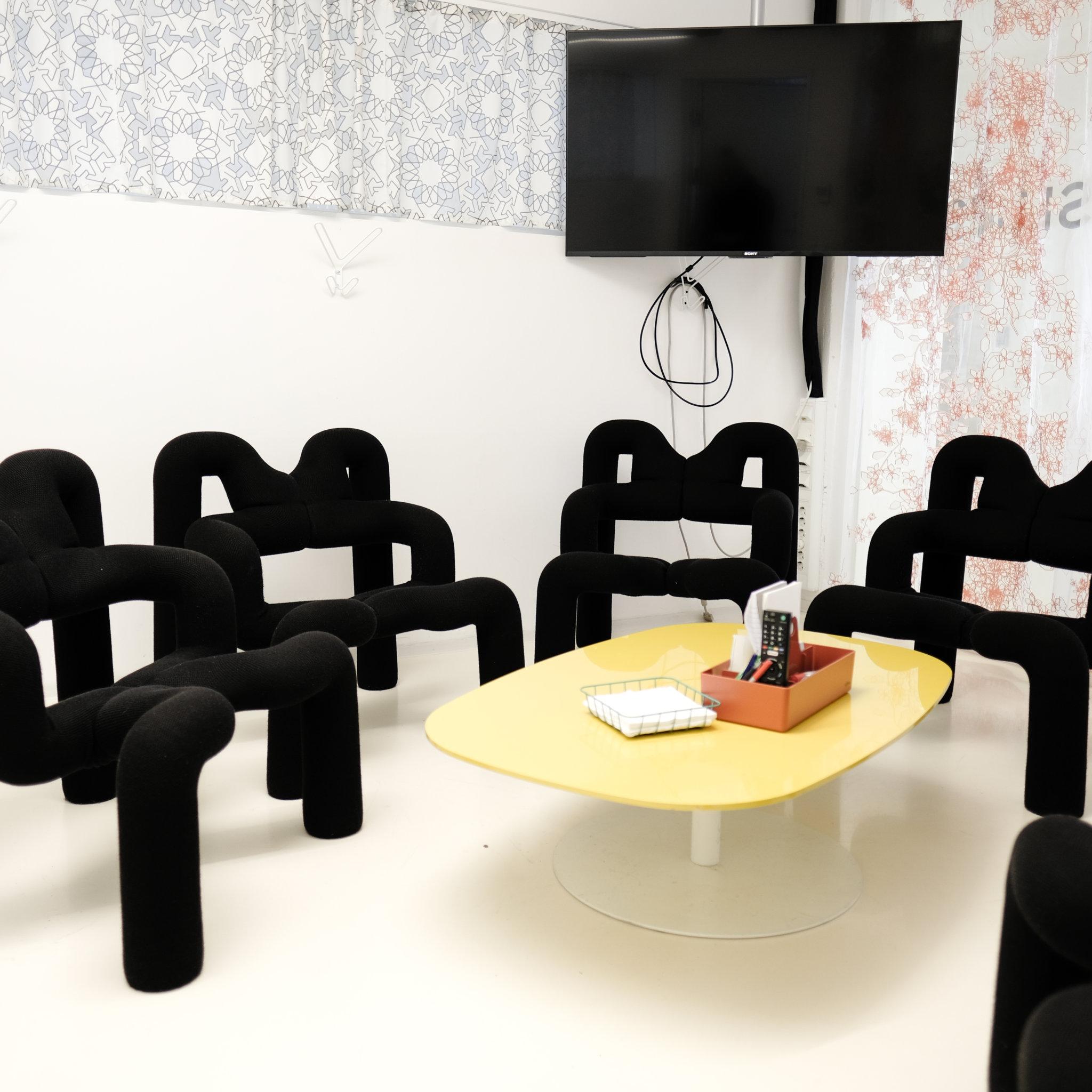 Svarta stolar vid ett gult bord.